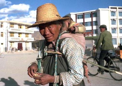 eine Tibeterin in Shigatse - dahinter die neuen Häuser der Han-Chinesen