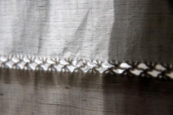 Le drap de famille brodé sert de rideau