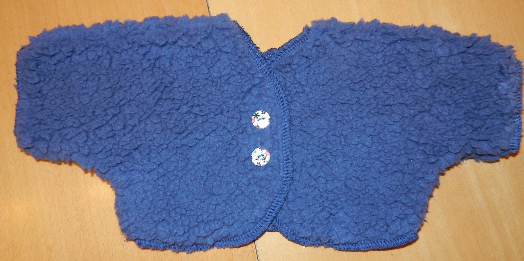 eine flauschige Jacke mit 2 Zierknöpfen, durch einen Klettverschluß kann die Jacke geöffnet oder geschlossen werden