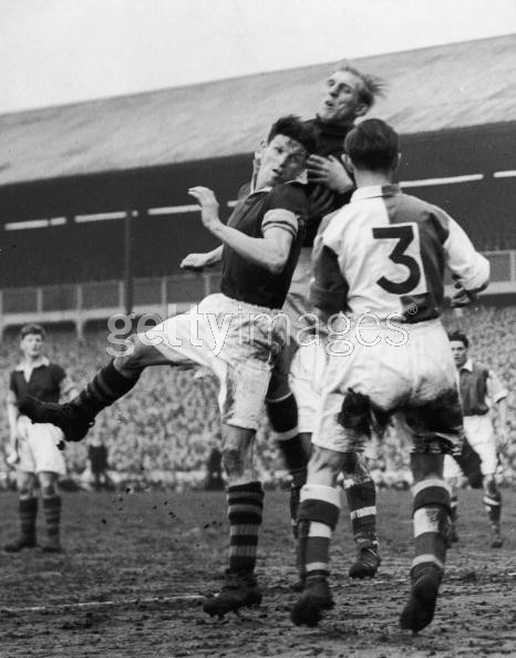 Blackburn goalkeeper Reg Elvy and defender Bill Eckersley, number 3, leap to defend a shot from a Burnley striker during a sixth round F A Cup tie between the two teams, 8th March 1952. Blackburn beat Burnley 3-1.