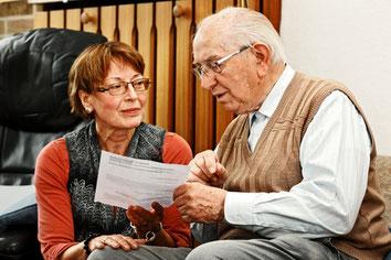 Ein Senior bespricht mit einer Frau die Steuererklärung