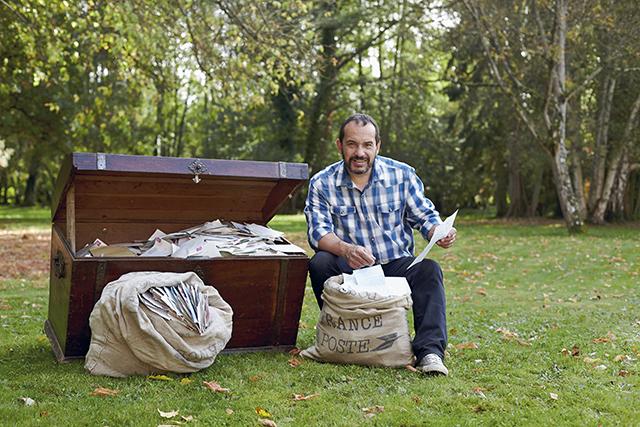 Mehdi dans le jardin du Moulin Bleu à Saint-Cyr-sous-Dourdan avec les centaines de lettres  que lui et sa mère ont reçues depuis des années des quatre bouts du monde.