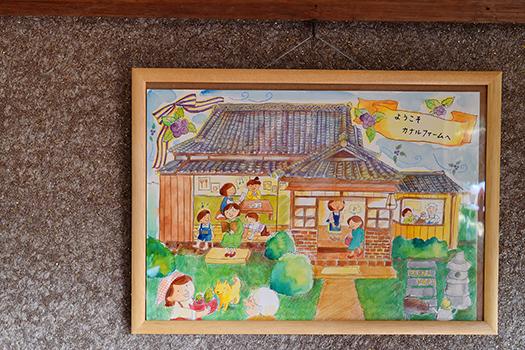 「さくら工房」三條さん作の絵画にはいろいろな人たちが集う、カナルファームの母屋が描かれています
