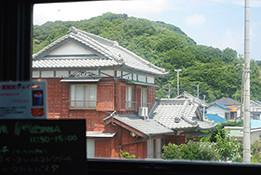 上)正面の海の景色も素敵ですが、私は側面の窓から見える、地元の民家が連なる風景も好きです。常緑の木々に映える瓦屋根も、温暖な外房・勝浦を象徴しているかのよう 左)店内ではビーチグラスのアクセサリーや、オリジナルTシャツなどの販売もあります