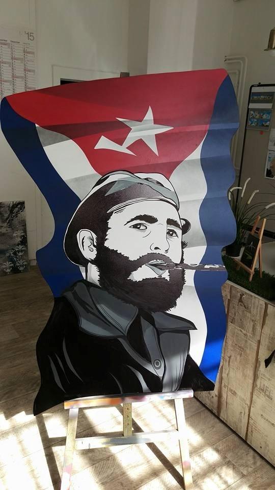 Graffitikünstler bemalt Holz nach Vorgabe mit Portrait und Bilder