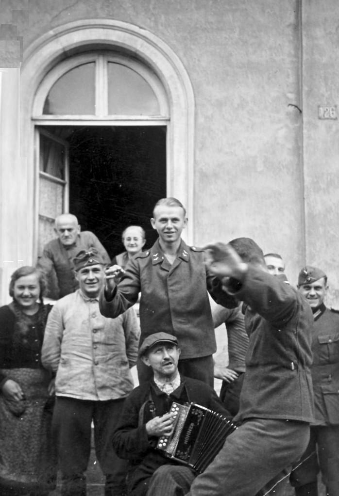 """Josef Hilschmann mit Harmonika, Elisabeth Klein, im Fenster Familie Sprißler (Damalige Aussage: """"Das war der 39er Krieg"""")"""