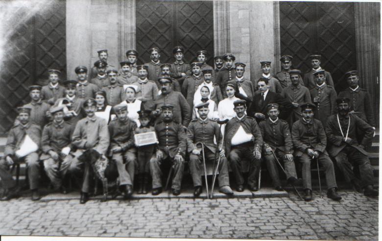 Sanitätsrat Rieder mit Patienten des Lazaretts im Alten Schulhaus vor der Geinsheimer Kirche aufgenommen