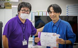 【画像】修了書を掲げる卒業生と内藤さん