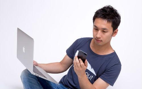 【画像】スマホとパソコンを見比べる男性