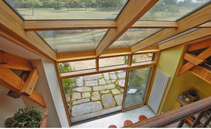 veranda verre en aluminium et bois intérieur par LA VERANDA ROCHELAISE signée RAPID miroiterie