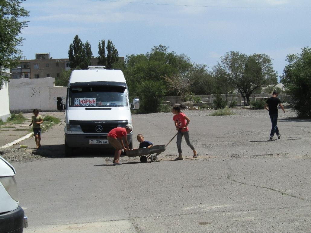 Kinder spielen auf dem Busbahnhof