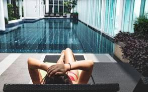 Tjej som solar framför pool