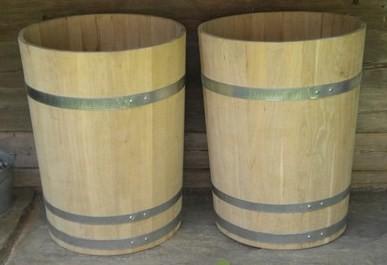 Wasserbottiche aus Kastanienholz, natur, mit verzinkten Eisenreifen. Maße: H 90 x D 70 cm.