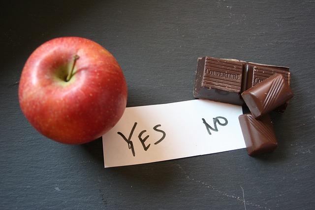 Apfel und Schokolade vor Zettel Yes und no zum Thema Süßigkeiten und Heißhunger und Gewohnheiten