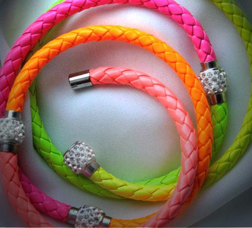 Neonfarbene Armbänder mit Strasssteinen besetzem Magnetverschluss