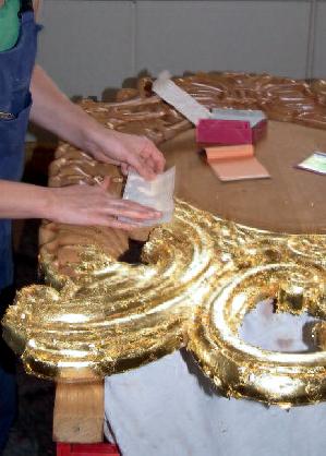 Die Mittelkartusche während der Vergoldung: Das Blattgold wird auf das angetrocknete Anlegemittel aufgebracht