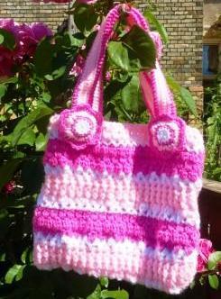 Kindertasche aus Acrylwolle mit Blumen an den Henkeln