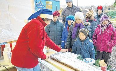 Eine Attraktion bei dem kleinen Weihnachtsmarkt: Elke Bodenlos schneidet den langen Stollen an. Der Erlös wird dem Kinderheim gespendet.Foto: bpa