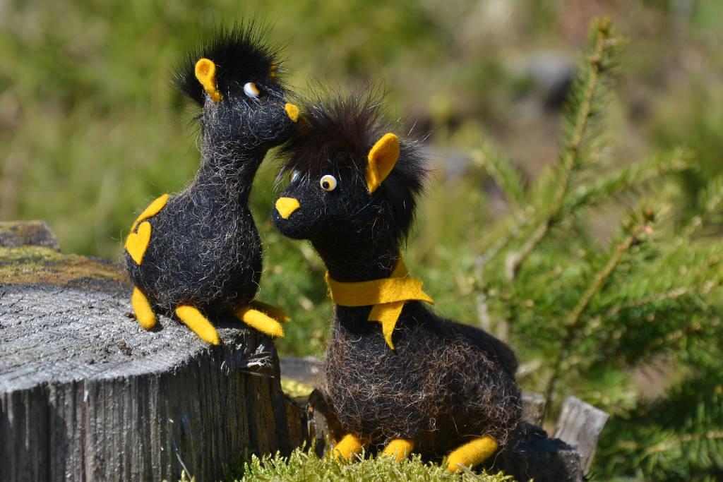 Alpakas aus schwarzen Filz mit gelben Ohren und Füßen sitzen auf Moos und einem Baumstamm