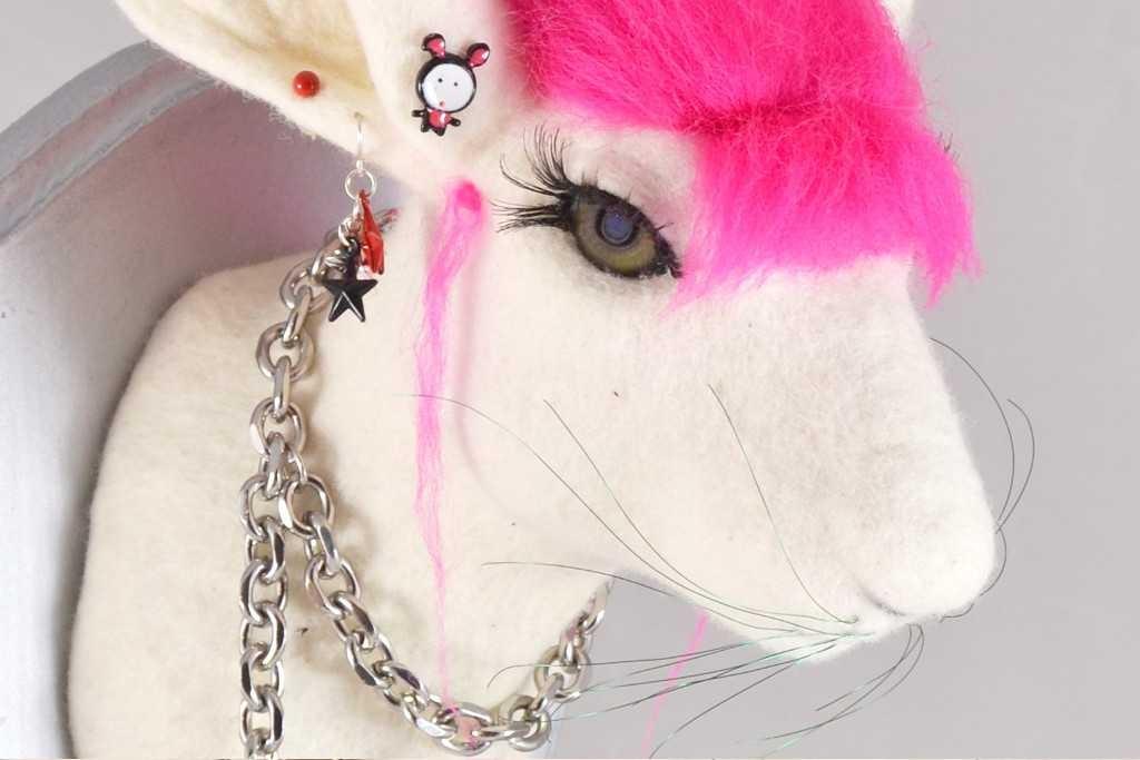 Gefilzter Hasenkopf als Wanddekoration. Mit rosa Haaren sieht der Trophäenkopf wie ein Punker aus.