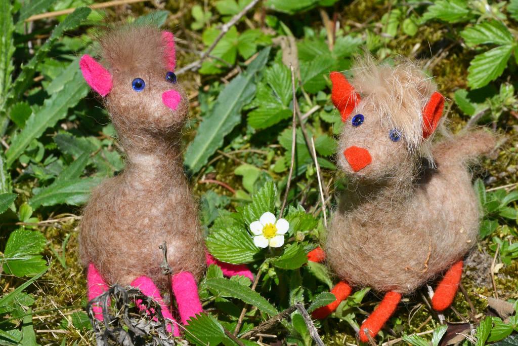 Zwei Alpakas aus braunem Filz sitzen auf einer Wiese
