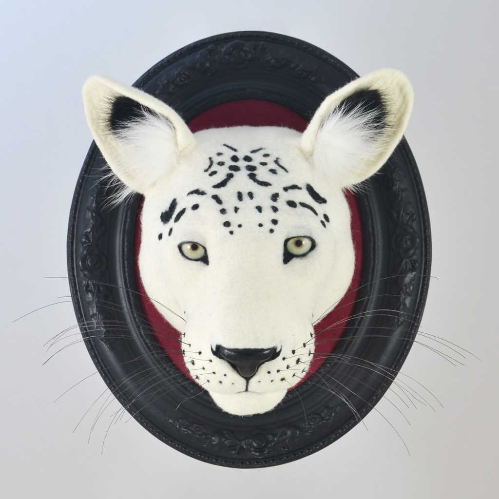 gefilzter Kopf eines Leopardenmit geschlossenem Maul, weiß mit schwarzen Flecken, Wanddekoration, schwarzer Holzrahmen