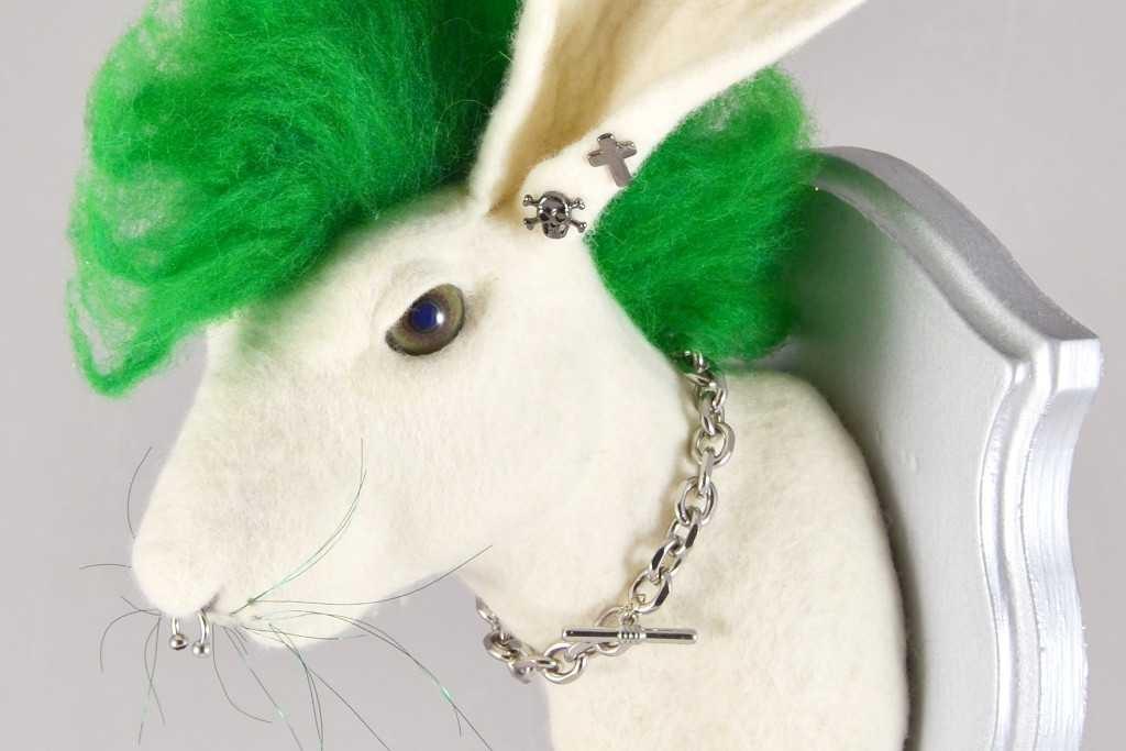 Tierkopf eines Hasen aus Filz mit grünen Punker-Iro, der wie ein Trophäenkopf auf eine Brett befestigt ist.