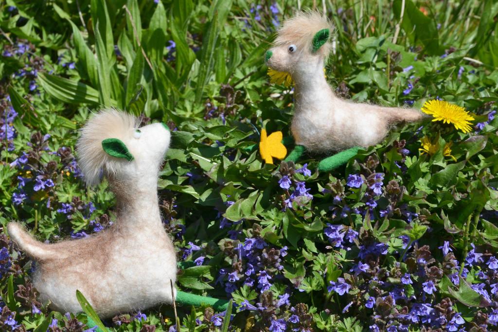 Zwischen blauen Blümchen sitzen weiße gefilzte Alpakas mit grünen Füße und Ohren