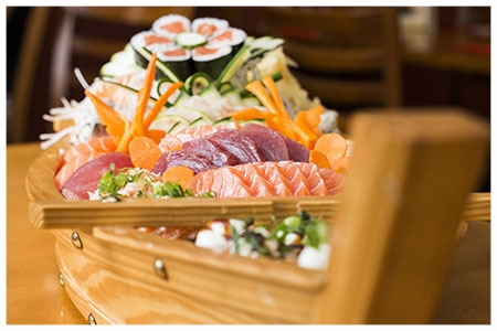 Assortiments de plat japonais présentés sur une barque de bois