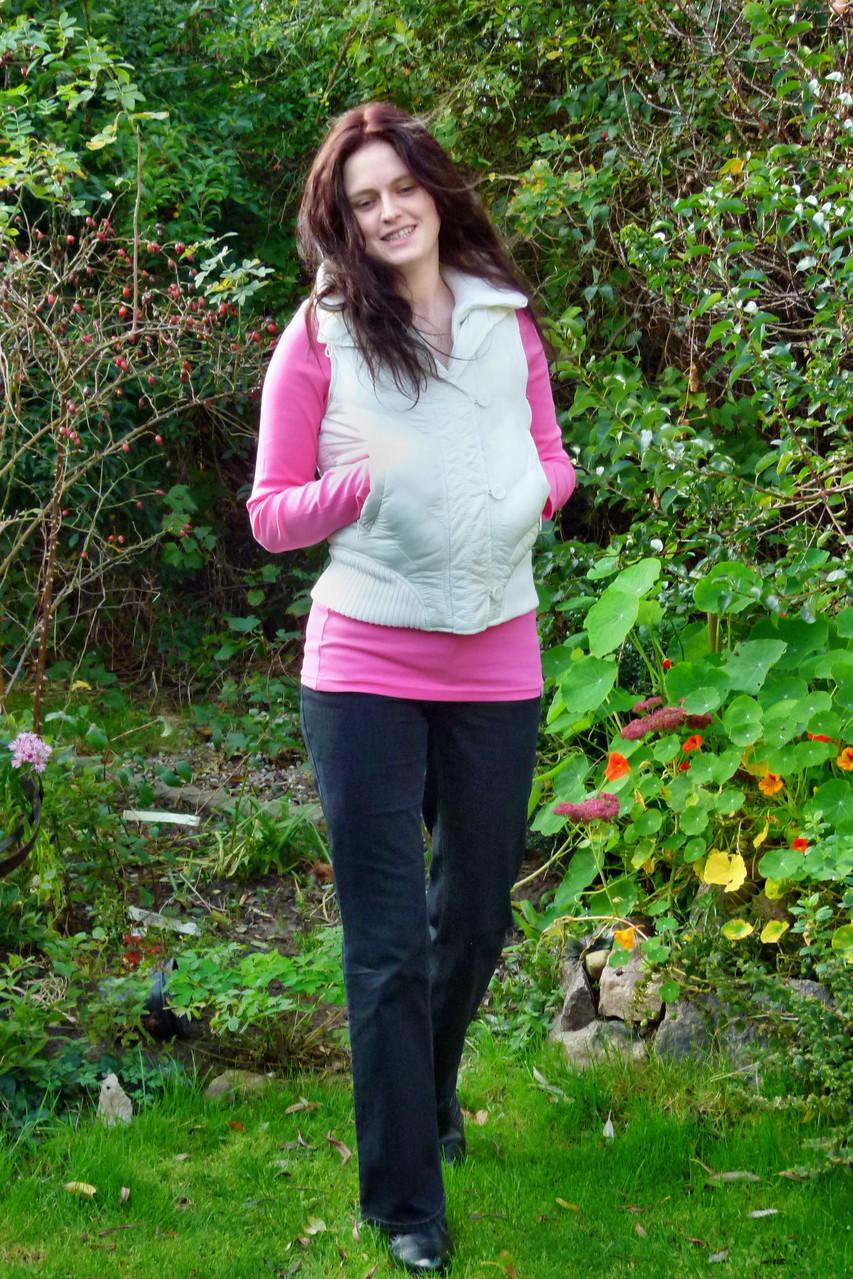 Wärmende Weste von Amisu über einem pinken Shirt, dazu schwarze Jeans von Mac und schwarze Stiefel