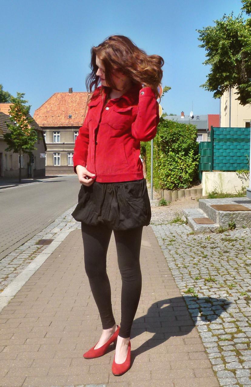 Outfit in schwarz und rot: Rote Feincordjacke, schwarzer Rock, rote Schuhe, kombiniert mit schwarzen Leggings und spitzen roten Riemchenpumps - ein wenig Retrolook