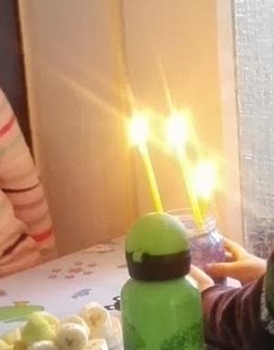 Drei Kinder im Alter von 3 bis 5 Jahren mit offenen Kerzen.