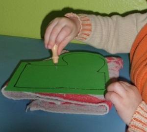 Ein Junge von 26 Monaten prickelt mit der spitzen Prickelnadel.