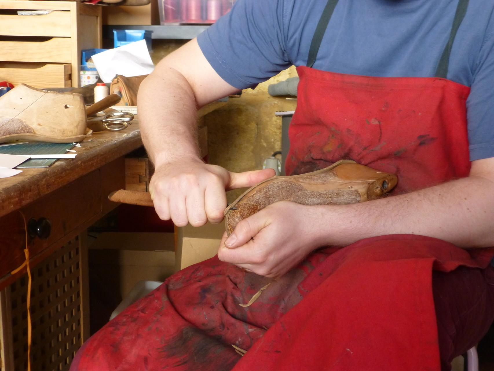 Il sculpte une forme, réplique en bois du pied du client