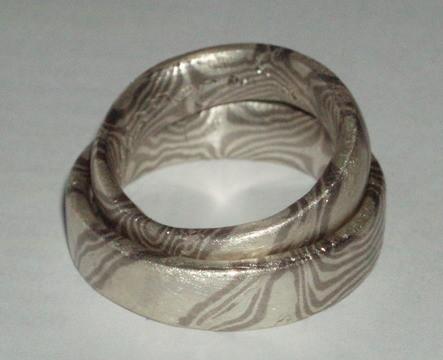 Silber-Palladium-Torsins- und Streifenmuster auf einem Ring.