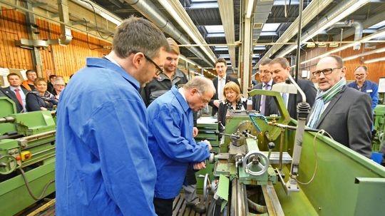 Moritz Merbach (3. von links), Feinmechaniker im Maschinenbau, befindet sich im zweiten Ausbildungsjahr. Er zeigt Landrat Sören Meng und dem Präsidenten der HWK, Bernd Wegner (Mitte links), wie eine Drehmaschine funktioniert.