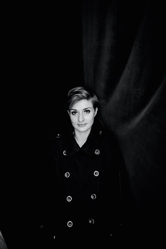 Junge Frau mit großen Augen blickt in die Kamera, in einem langen schwarzen Mantel mit grossen Knöpfen  - Boudoir in schwarzweiss www.dirk-brzoska.de - Copyright DIRK BRZOSKA FOTOGRAFIE Leipzig Germany Fotoshooting Bewerbungsfotos