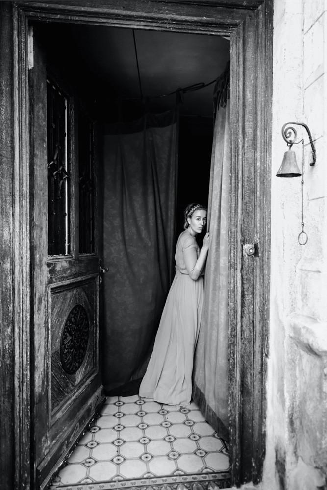 Junge Frau mit langem Kleid geht durch grosse Landhaus Holztür mit Glocke und blick zurück über ihre Schulter in die Kamera - Boudoir in schwarzweiss www.dirk-brzoska.de - Copyright DIRK BRZOSKA FOTOGRAFIE Leipzig Germany Fotoshooting Bewerbungsfotos