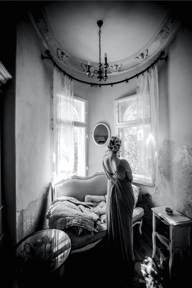 Junge Frau mit langem Kleid steht mit dem Rücken zur Kamera in einem Landhaus vor dem Fenster und sieht in einen Spiegel - Boudoir in schwarzweiss www.dirk-brzoska.de - Copyright DIRK BRZOSKA FOTOGRAFIE Leipzig Germany Fotoshooting Bewerbungsfotos