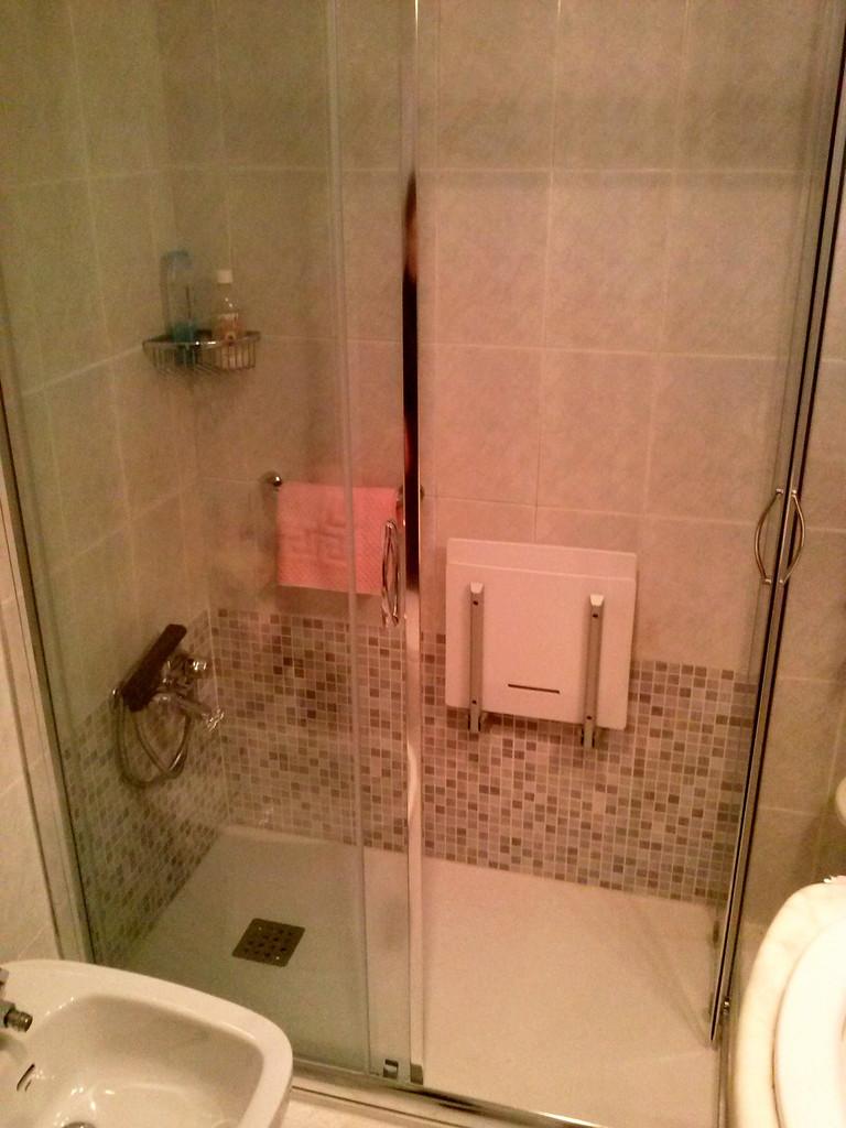 plato de marmol tecnico antideslizante y mampara en escuadra con asiento de ducha