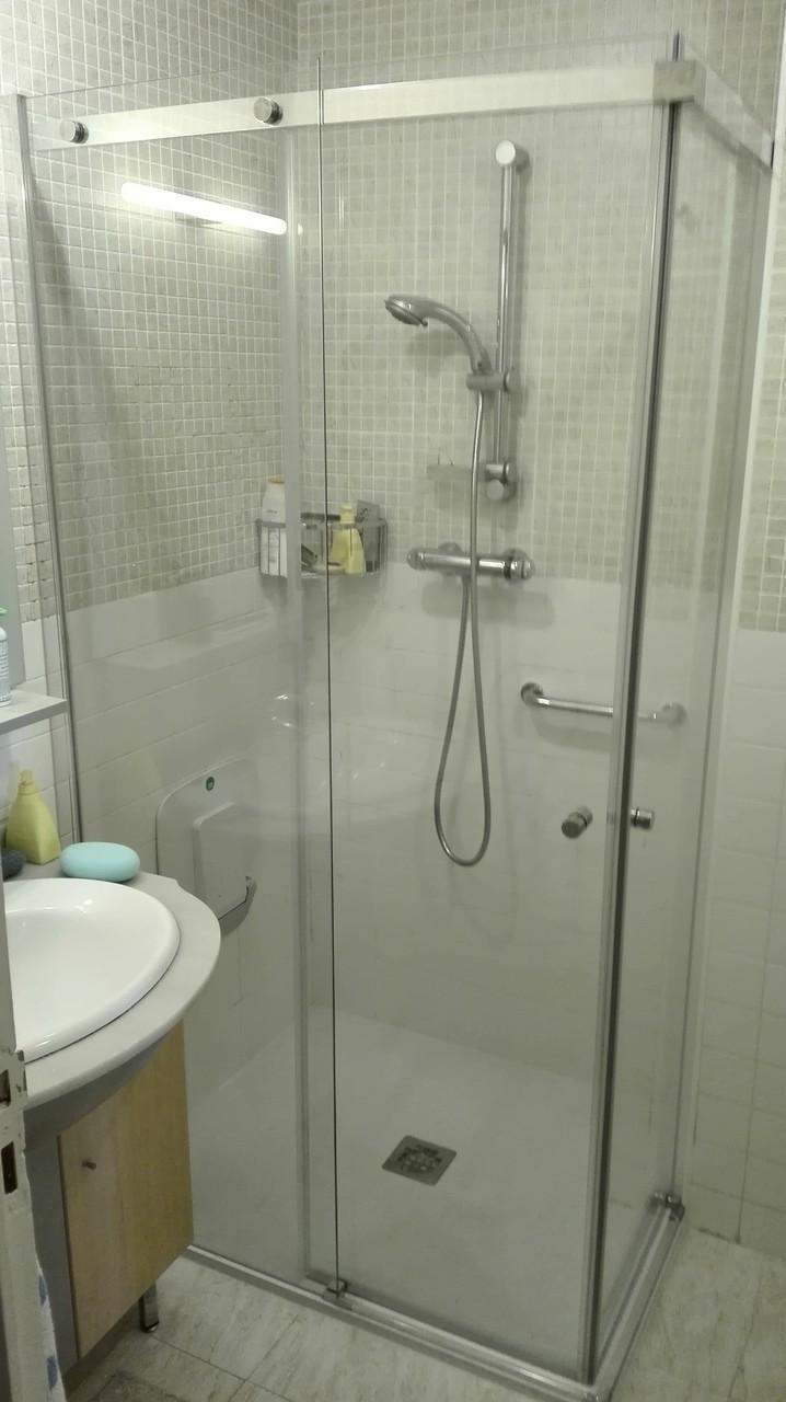 plato de ducha con mampara especial en escuadra en la que la puerta se solapa con la pared