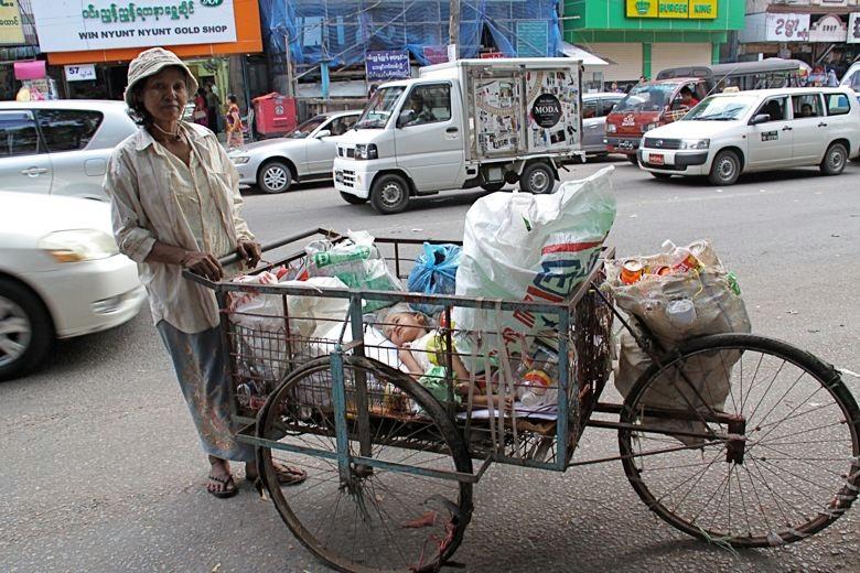 リサイク可能なゴミを拾い集めるお母さん。台車の中で子どもが寝ている。