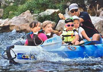 Descente de l'Ardèche accompagnée d'un guide en canoë pour les enfants, avec passage sous le pont d'arc