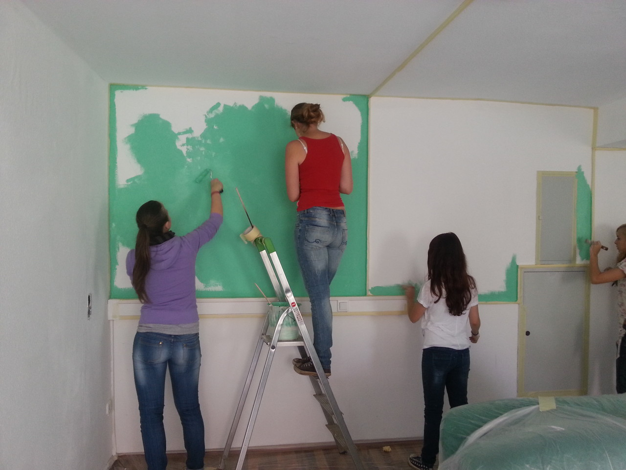 Während drei Wände weiß gestrichen werden, erhält die dritte den Grünton unseres Logos