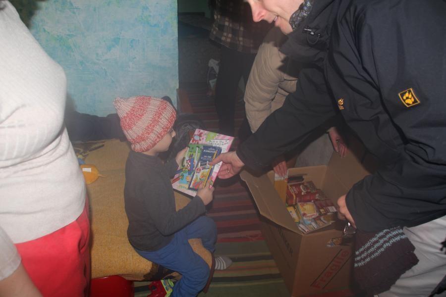 Kind erhält Malbuch und Stifte