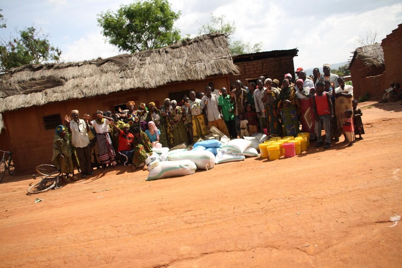 Reise nach Tansania: Gruppenfoto mit Dorfbewohnern und Spendengütern