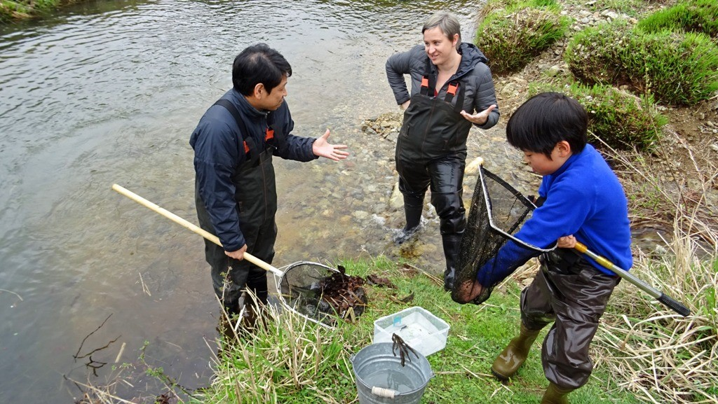 Dr. Okada explaining his research in Ichikawa River to a conservation biologist from the US, with his son, Ryoga, assisting them.