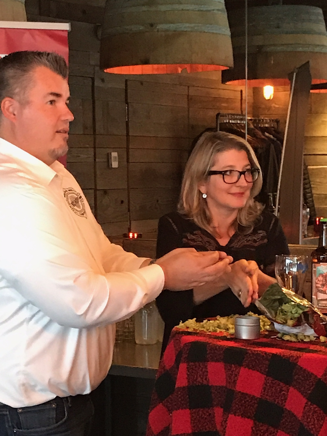 Dwayne Stewart, General Manager, BC Hop Co teaching Minister of Agriculture Lana Popham the art of rubbing a hop!