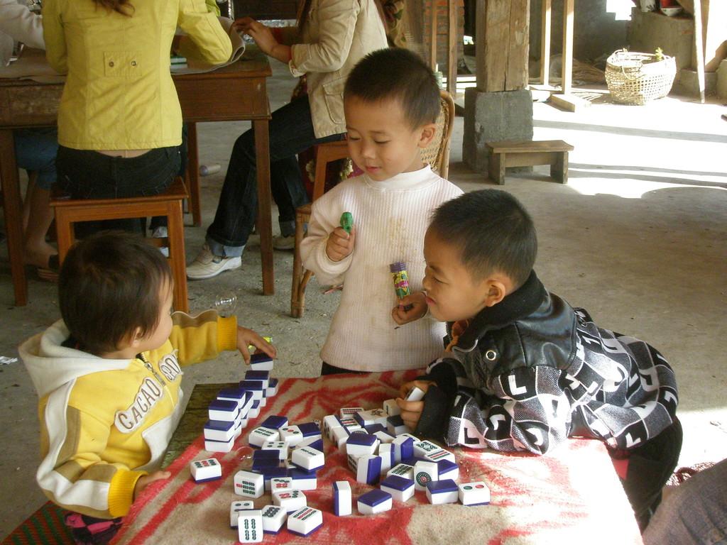 大人の真似をして麻雀牌で遊ぶ子供たち。
