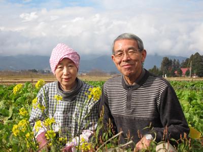 べんり菜の花の前で妻、久美子さんと共に
